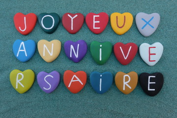 Joyeux Anniversaire, french Happy Birthday with multicolored stone hearts over green sand