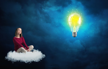 Woman sitting on a cloud lokking at huge lightbulb