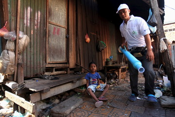 A girl sits in front of her home as a health official collects mosquitos and larva to check for Zika virus at a village in Phnom Penh, Cambodia