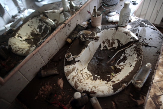 Sink is seen covered in mud in a bathroom of a house following extreme rainfall in Olbia on Sardinia island