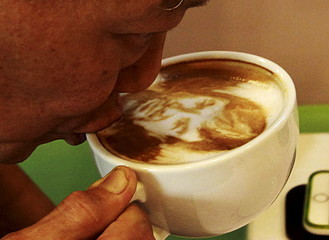 A man sips a cup of coffee with latte art depicting a caricature of Filipino World Boxing Champion Manny Pacquiao at Bunny Baker cafe in Manila