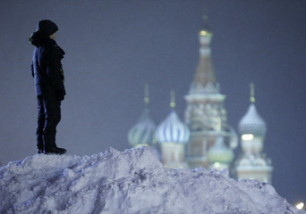 A boy stands on top of a heap of snow in the Red Square, with St. Basil's Cathedral seen in the background, in central Moscow