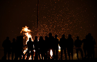 People looking at a bonfire during the traditional San Juan's night in Gijon