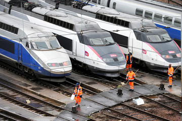 Workers pass by French TGV trains parked at a SNCF depot station in Charenton-le-Pont near Paris
