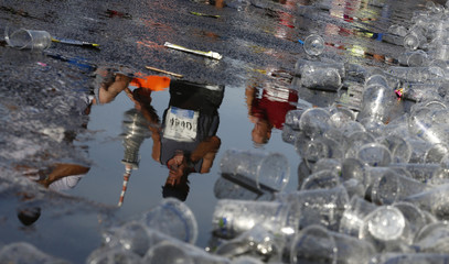 Runners are reflected in a puddle as they pass a drinks station during the 41st Berlin marathon