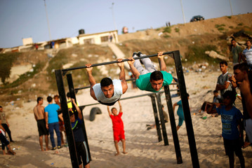 Members of Bar Palestine team demonstrate their street workout skills during a training session on a beach in Gaza City