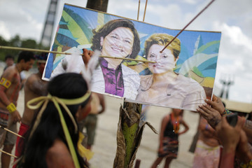 An indigenous woman pokes an image of Abreu and Rousseff  with an arrow during a protest in Brasilia