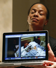 Dayana Mejia holds up a laptop showing a photograph of her hospitalized partner Edwin Mieses, during a news conference in New York