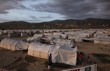 Earthquake victims sheltered at Camp Corail walk among their tents