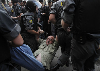 An activist is detained by police during a protest action to defend Article 31 of the Russian constitution in Moscow
