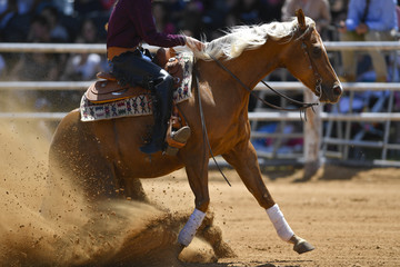 The side view of a rider in cowboy chaps and boots sliding the horse in the sand