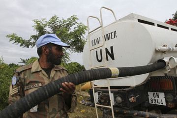 A United Nations peacekeepers soldier prepare to distribute water to the population of Tai