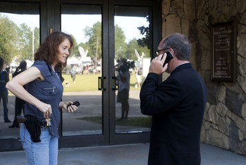 Reverend Mahoney of the Christian Defense Coalition speaks with an armed member of the Dove World Outreach Center while attempting to speak with the church's pastor Jones in Gainesville