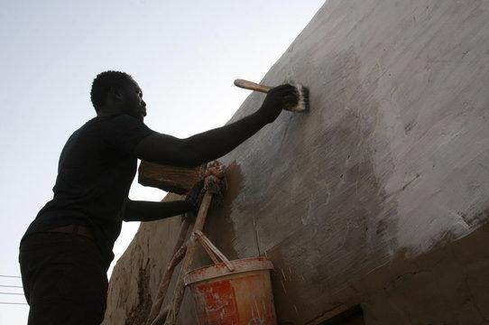 A worker paints a wall with limestone liquid in Omdurman