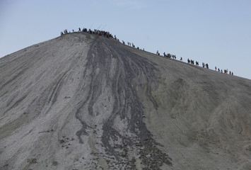 Pakistani Hindu devotees walk on a mud volcano to perform a ritual offering of coconuts before visiting Shri Hinglaj Mata Temple located in Balochistan province