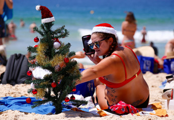 Irish backpacker Genna Woods adjusts her small Christmas tree she planted in the sand as she celebrates Christmas Day at Sydney's Bondi Beach in Australia