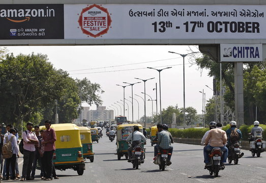 Traffic moves on a road beneath an advertisement of online marketplace Amazon, in Ahmedabad, India