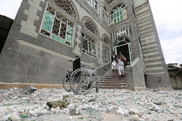 People walk out of their house damaged by an airstrike in Sanaa