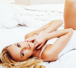 young pretty blond woman in bed covered white sheets smiling che