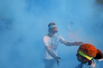 A woman runs through colored powder during the Color Run race in Tegucigalpa, Honduras