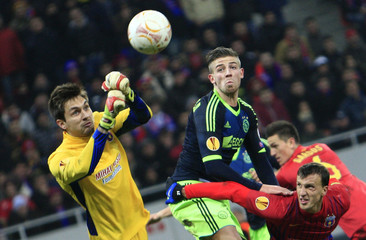 Steaua Bucharest's goalkeeper Tatarusanu clears a ball in front of his team mate Chiriches and Ajax Amsterdam's Alderweireld during their Europa League soccer match in Bucharest