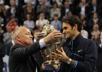Switzerland's Federer receives the winners trophy from tournament director Brennwald after his victory in his final match against Nishikori of Japan at the Swiss Indoors ATP tennis tournament in Basel