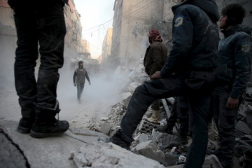 Residents look for survivors in a site hit by what activists said were airstrikes carried out by the Russian air force in the town of Douma, eastern Ghouta in Damascus, Syria