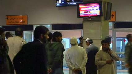 Passengers look at news on TV screens inside a terminal at Benazir Bhutto International Airport, following a Pakistan International Airlines plane crash in northern Pakistan, in this still frame taken from video
