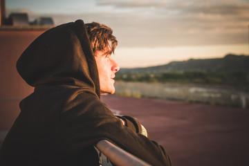 Chico joven mirando al horizonte al atardecer en la azotea