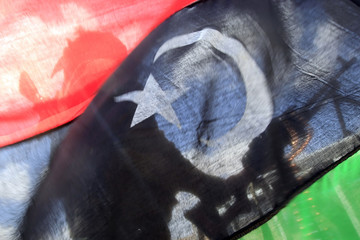 A rebel fighter is seen behind a Kingdom of Libya flag near the front line along the western entrance gate of Ajdabiyah