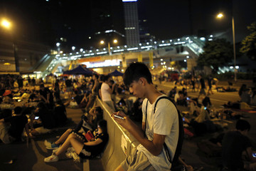 Protester looks at his mobile phone screen as he joins others to block areas around the government headquarters in Hong Kong