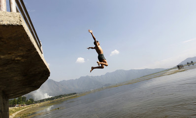 Boy jumps from a jetty into the waters of Dal Lake to cool himself on a hot day in Srinagar