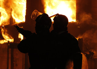 Police officers wearing riot gear stand in front of a burning building in Tottenham