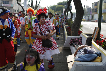 A clown looks at a homeless woman sleeping on a bench during a pilgrimage to the Basilica of Our Lady of Guadalupe in Mexico City