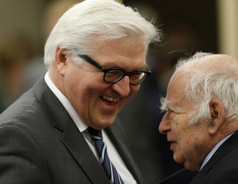 German Foreign Minister Frank-Walter Steinmeier greets an unidentified man before giving his speech in Washington