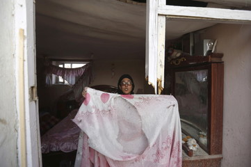 """An Afghan woman shows a bed cover after a suicide attack on French restaurant  """"Le Jardin"""" in Kabul"""