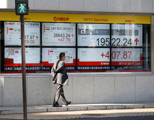 A man walks past an electronic board showing stock prices outside a brokerage in Tokyo