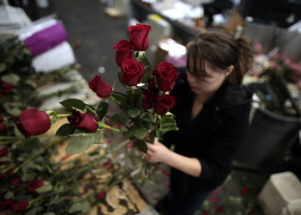 Celeste Roldan attaches water vials to roses from Ecuador at Liberty Wholesale in the flower market in preparation for Valentine's Day in Los Angeles