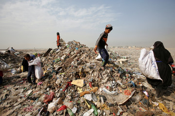 Garbage pickers collect recyclable materials at a rubbish dump in the outskirts of Baghdad