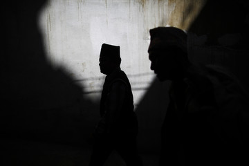 People are silhouetted as they walk on a street in the ancient city of Bhaktapur