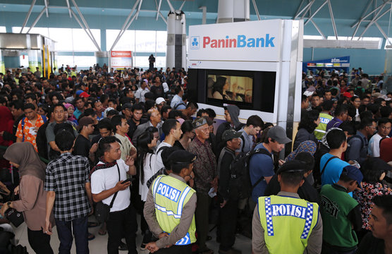 Hundreds of Lion Air passengers stand in a line to claim their tickets money back after their flights were delayed at Soekarno-Hatta airport in Jakarta