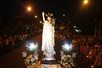 The Faithful stands around an image of the Risen Christ during a procession on Easter Sunday in Manila