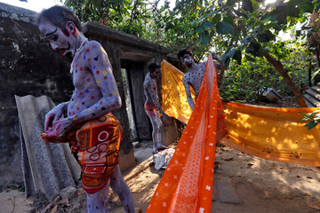 Devotees with their bodies painted prepare to wear saree, a traditional Indian cloth used for women's clothing, before taking part in a ritual as part of the annual Shiva Gajan religious festival at Sona Palasi village