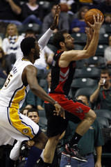 Raptors' Calderon of Spain puts up a shot defended by Pacers' Hibbert during the fourth quarter of their NBA basketball game in Indianapolis