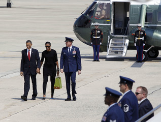 U.S. President Barack Obama and first lady Michelle walk before boarding Air Force One at Andrews Air Force Base in Maryland