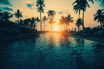 Tropical beach with silhouetted palm trees during sunset.
