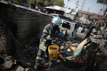 A firefighter carries a bucket of water to put out fire caused by the explosion of a gas tanker truck in San Pedro Xalostoc