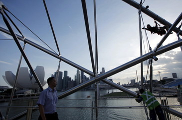 A man passes by as maintenance work is carried out on The Helix Bridge near Singapore's central business district