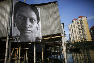 A photograph of a garment worker taken by a student of the Counter Foto photography department is seen by the waterfront of Korail slum at Gulshan area in Dhaka