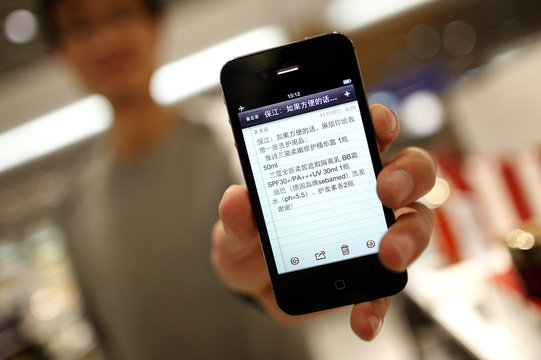 Customer from China shows a shopping list on his smart phone in a Duty Free store at the Fraport airport in Frankfurt,